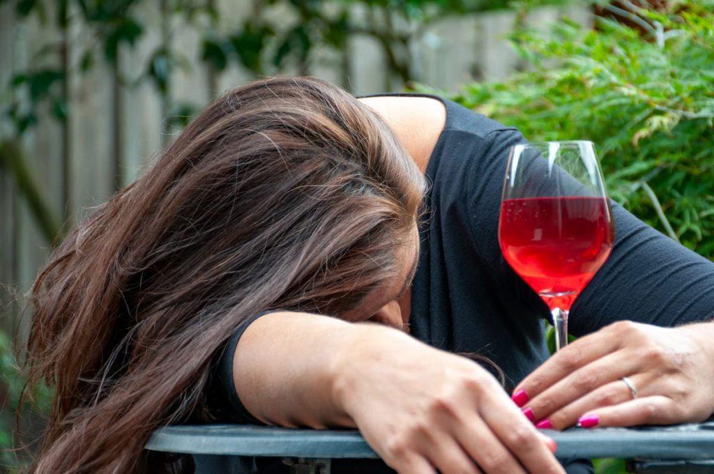 Pijana kobieta opierająca głowę o stół
